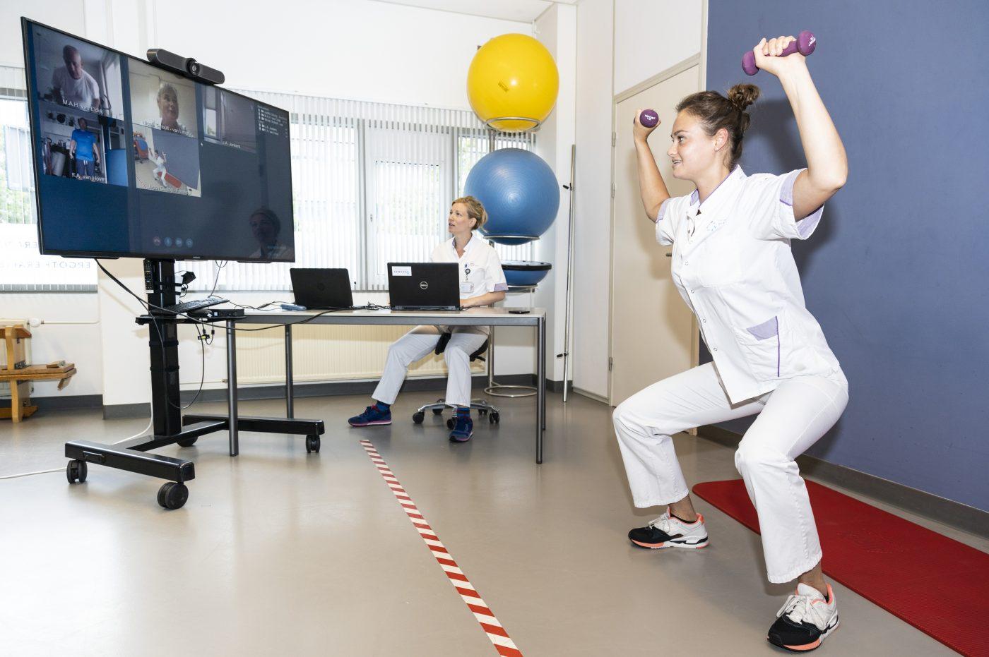 Fysiotherapeut doet oefeningen voor. De patiënten kijken mee via een videoverbinding. Zij doen thuis de oefeningen mee.