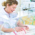 NICU verpleegkundige met pasgeborene in couveuse