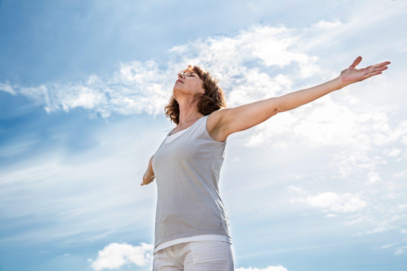 Vrouw haalt diep adem met uitgestrekte armen